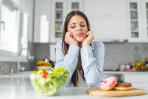 Woman deciding between eating apples or sugary donuts that cause plaque buildup.